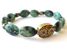 Stunning beaded stretch bracelet featuring oval African turquoise beads, oxidized brass beads, and a handcrafted Tibetan focal bead with brass (inlaid with turquoise and coral chips) by Rock & Hardware Jewelry.