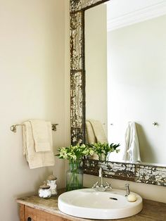 Salvage Style  Mirror, Mirror  An oversize mirror reflects light and makes the room feel large. Its weathered antique frame reinforces the vintage theme and makes the mirror a focal point. The vanity boasts a large drop-in sink, complete with a soap dispenser and plenty of counter space. Antique hot and cold knobs -- seen through the mirror -- find new life as handy hooks for towels and robes.