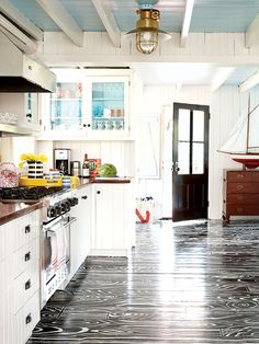 what if you did a faux bois on the painted living room floor?  they have rollers that put the pattern down.  Funky coastal kitchen. painted floor and ceiling!