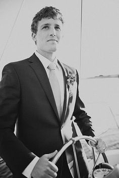Groom steering sailboat.  What a hunk.