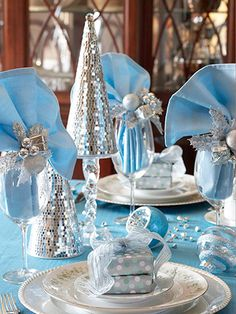 Winter Wonderland Table. Turn your table into a winter landscape by decking it out with a cool blue tablecloth and icy white plates topped with silver wrapped favors. Add height to the table with fanned out blue napkins tucked into glasses and adorned with silver napkin rings. Scatter frosty ornaments and silver trees across the table, and Jack Frost will be begging for an invite to your party.