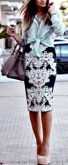 Bold pattern skirt, sheer blue knotted blouse, and blush wedges.
