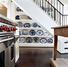 Creative use of the understair area to display beautiful blue and white dishes.