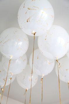 Gold splattered white balloons