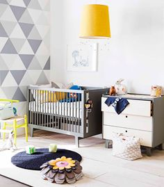 ultra modern nursery - love the grey and white harlequin wall and pop of mustard in the lampshade.