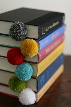 Things to do with leftover pieces of yarn: Pom-poms make bookmarks you won't want to stop playing with.