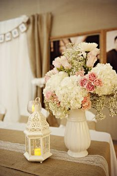 Wedding flowers. Hydrangeas, baby's breath, roses.  Add some burlap and lace and we're all set. :)