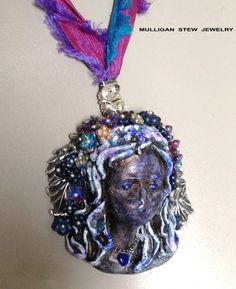 I made a Polymer Clay lady, then created a necklace using B'SueBoutiques silver leaves, glass flower beads and Sari Ribbon.  Kate from MulliganStewJewelry.com