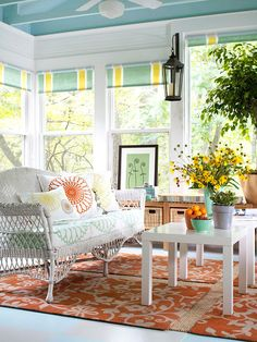 this is such a cheerful enclosed porch filled with sunny colors and plenty of pattern