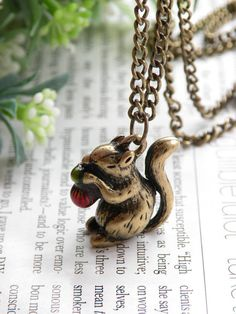 A necklace featuring a squirrel eating a pine nut.
