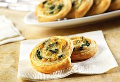 Spinach-Cheese Swirls - They feature a spinach, onion and cheese filling simply rolled up in flaky puff pastry and sliced into pinwheels.