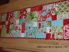 Make a Quick and Easy Christmas Table Runner to practice your patchwork this Christmas. This pattern for a quilted table runner involves simple disappearing nine-patch piecework with Christmas fabrics.