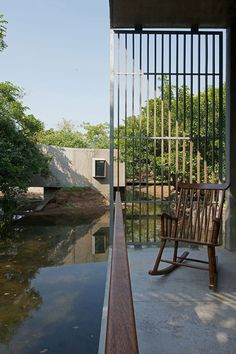 A bridge over a stream connects the two sides of this concrete house in India.