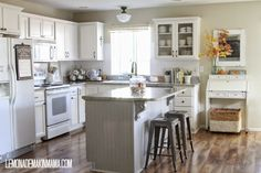 Pretty white kitchen with painted cabs, greige island, white appliances, schoolhouse lights