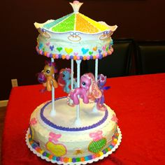"""My Little Pony cake I made for my daughter's 6th bday! I bought a """"carousel kit"""" at Michael's and used my daughters pony's as toppers!"""