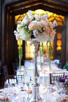 Tall silver stands hold bountiful floral arrangements and simple table numbers.
