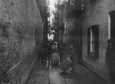 Alley playground: Children play with barrels under the washing hung between tenements in Gotham Court, Cherry Street around 1890. (New York)    Read more: http://www.dailymail.co.uk/news/article-2089243/Slumdogs-New-York-The-remarkable-images-capturing-immigrant-families-unrecognisable-19th-century-New-York.html#ixzz2LDGxfx2h   Follow us: @MailOnline on Twitter   DailyMail on Facebook