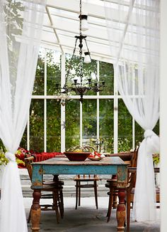 sun room/conservatory transformed into a dining space with beautiful old table at the centre of the design
