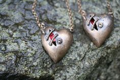 Hand cast in bronze and adorned with a shimmering ruby seashell inside the heart. https://www.etsy.com/listing/121890959/dark-sea-sutured-heart-necklace-bronze