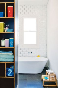 """6. """"I hate showerscreens. They're so hard to keep clean,"""" says owner Sam of Klopper & Davis Architects, who split this bathroom in half. """"On one side is the bath and open shower, and everything can get wet. On the other is the storage, vanity and toilet, and all that stays dry."""" Pigeonhole-style cabinetry gives the area an open feel."""