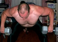 hairy beefy man lifting weights