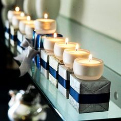 This menorah uses wrapped boxes with tealights on top. Silver painted wooden blocks would make a sturdier base.