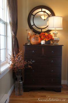 small dresser in entryway under a mirror