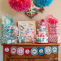 Decorate your baby shower gifts station in equal parts pink and blue by creatively combining Safari baby shower banners, cutouts and hanging fluffies for a gender reveal baby shower.