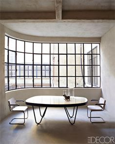 Inside a former hat factory in Italy, architect Michael Rieper and designer Vincenzo de Cotiis created a spare, contemporary loft with a solarium-like dining area.