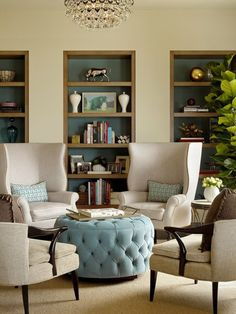 Aqua and Cream... and elegant color combination. Great built in bookcases... I love the oversized wing chairs and the oh so wonderful- round, aqua tufted ottoman.