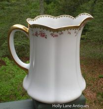 An Antique Haviland Limoges Large Pitcher    This most special antique pitcher dates to c.early 1900's.    This Haviland pattern has pink roses encircling its top rim. There is also a heavy gold border at the top rim and the handle is gold encrusted.    The shape of this pitcher is exquisite with melon ribbing ending in scallops near the base and at the top rim.  $268.00