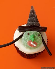 Green Witch Cupcake  To make this wicked candy witch, use a green gumdrop for a face, a piece of red gumdrop and a white sprinkle for the mouth, licorice for her hair and hat brim, and a black gumdrop molded into a triangle for the pointy witch's hat. Add two black sprinkles for the eyes, and a green mint for a nose.