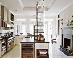 Open shelves from the island to the ceiling; dark fireplace