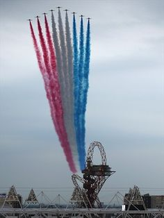 The Red Arrows fly over the Olympic Stadium and the ArcelorMittal Orbit Tower ahead of the opening ceremony of the 2012 London Olympic Games on 27 July,