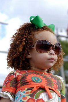 Red curls, shades, cheeks & a green bow. What a cute kid!