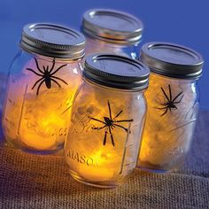 DIY spider jars for Halloween party decor using thrifted mason jars.