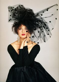 I know this is an old photo, maybe I am stuck in this decade  But this evening gown, the low shoulders and deep neckline with big earrings, big hair and a polka tulle hat is perfection for me...classy and artistic...