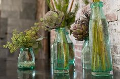 Add flowers to these green glass milk bottle vases to create a wonderful centerpiece for weddings, home and event decor. Each bottle is unique with light blemishes and bubbles created from using recycled glass, adding to their antique-like appeal. #centerpiece #vase #milkbottle