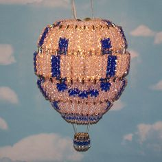 Hand-made hot air balloon lamp in crystal and royal blue. It's made from 156 silver safety pins and 1,428 acrylic beads and is designed to hang from a ceiling hook or wall bracket. Uses a 7-watt night light bulb on a 6-foot clip in cord.