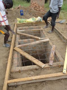8. To make the concrete slab on which the main part of the latrine will stand, a wooden mould is created around the two pits and they are covered with wire and lengths of wood.