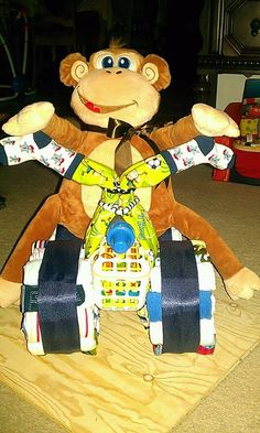 Moto Monkey Baby Diaper cake. Made with diapers, washcloths, onesies, bibs, socks, bottles, baby blanket and assorted baby items. Makes great gifts and convo piece.