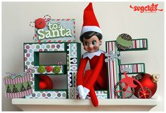 """I decided to make this little """"home"""" for our Elf. This elf comes with many rules. After the elf mysteriously appears under your tree you have to name the elf and the kids are not allowed to touch it. The elf watches the kids and reports back to Santa on their behavior. At night, the elf hops down from the shelf and gets into mischief or hides somewhere in the house. Last night he got into the Hershey Kisses and put wrappers all over the counter!"""