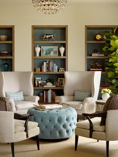 Great built-in shelves, comfortable wing back chairs & cushioned smaller arm chairs, nice shelf accessories, simple cool colored ottoman with color matching pillows. Well done.