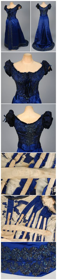 WORTH TRAINED and BEADED SATIN BUSTLE DRESS, 1880s 2-piece sapphire blue silk, boned bodice covered in black tulle studded with beads and sequins. Woven Petersham label. (Bodice restyled: sleeves replaced, velvet trim added, tarnish to sequins, bodice lining torn, wear and repair at hem). Whitaker Auctions.