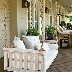 White Farmhouse Porch Swing | This plush white porch swing provides extra seating for this spacious wrapped covered porch—perfect for entertaining. | SouthernLiving.com