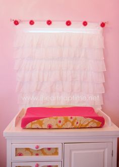 DIY - Tutorial on curtains & changing pad. Blogger made a changing pad that matched fabric she glued to the changing table. I may do a similar idea with changing pad & matching fabrics in baskets for the shelving.
