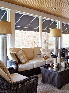 A wicker set by Summer Classics provides seating on this screened side porch. Cast-off columns were repurposed as floor lamps.