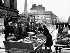 A greengrocer remains open for business at a market in Lambeth Way in London after a V-2 Bombing raid.