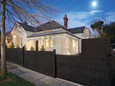 White on white Victorian house with black roof and picket fence