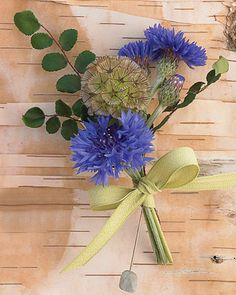 Blue cornflowers and scabiosa pods mixed with button fern leaves; a crepe ribbon encircles the stems.